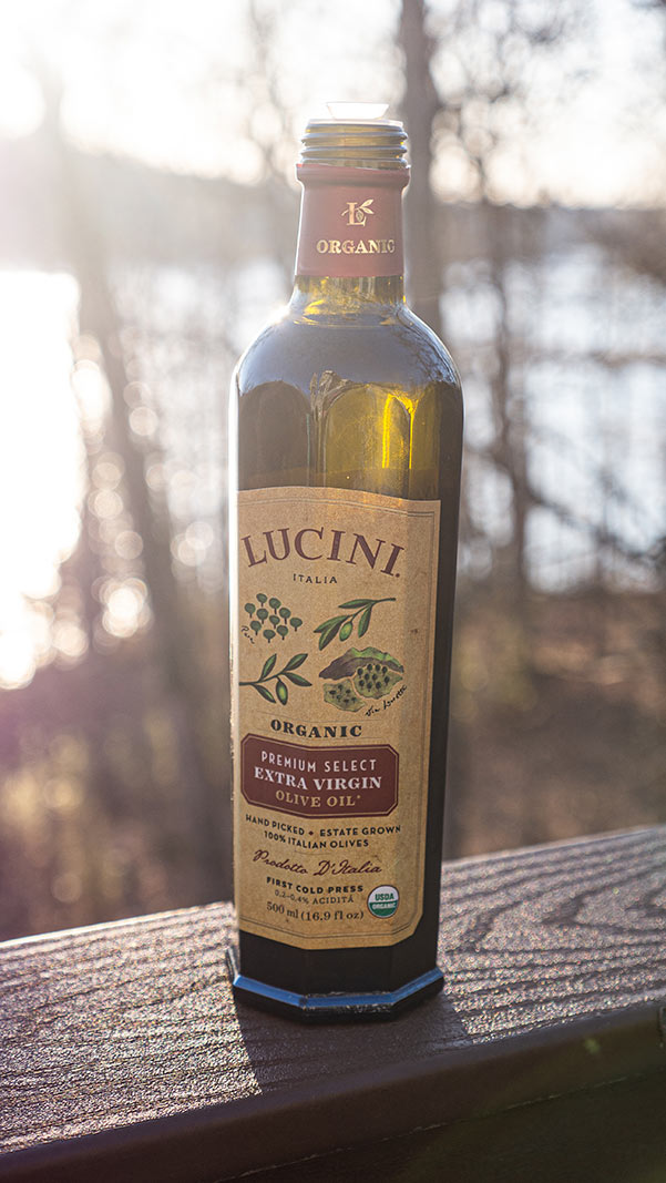 bottle of olive oil on a deck railing