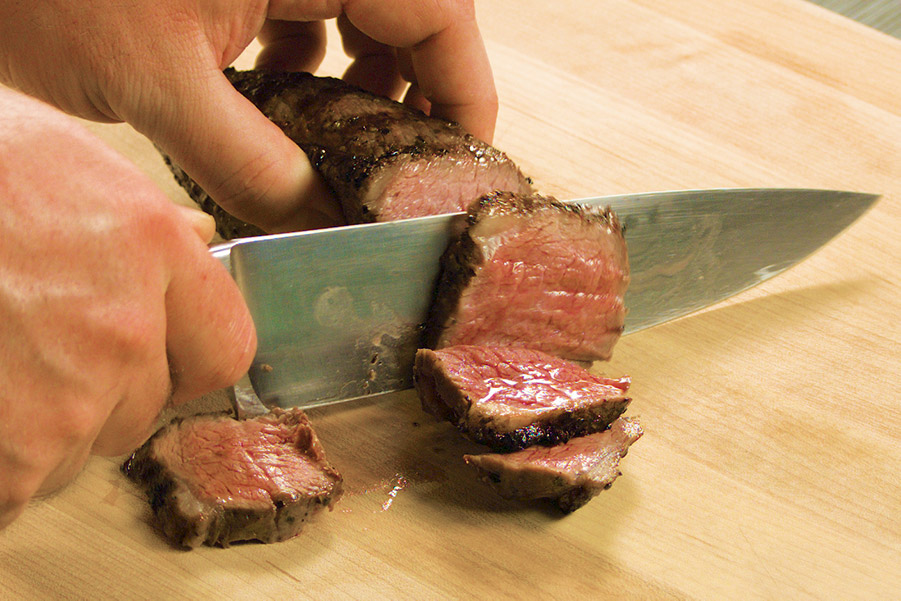 Chef knife slicing perfectly grilled picanha steak