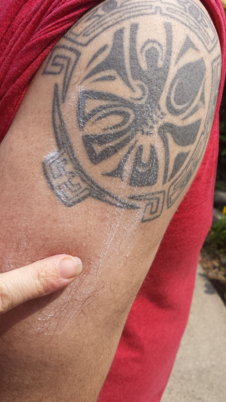 rubbing sunscreen on tattoo and shoulder
