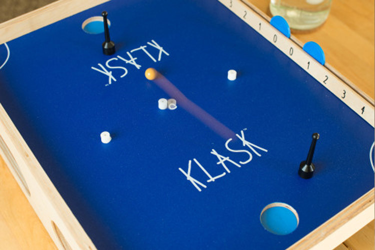 klask-is-played-by-two-magnetic-game-pieces-moving-across-a-gaming-table-hitting-a-yellow-ball-back-and-forth-until-it-falls-into-the-opponents-goal