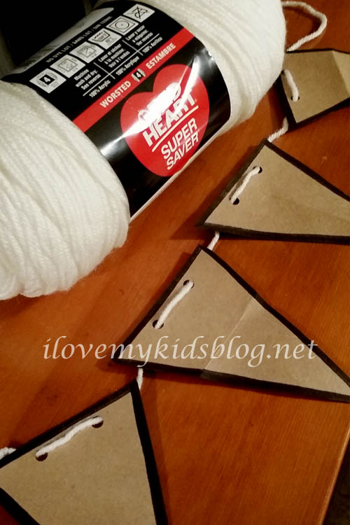 Assembling the Upcycled Paper Banner with yarn