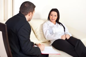 Patient woman sitting on couch and talking with psychologist man