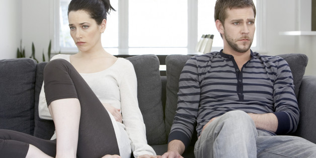 Couple sitting on sofa looking angry, touching hands