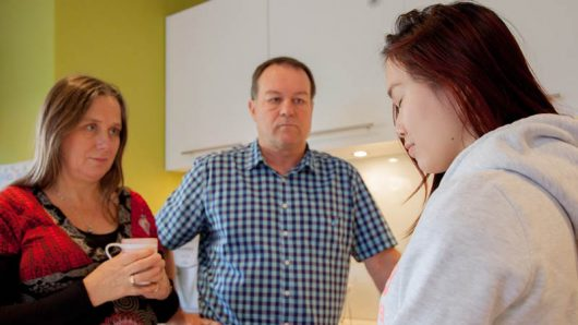 Over the shoulder of daughter talking to parents in kitchen