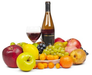 Bottle and a glass of red wine among the fruit - still life