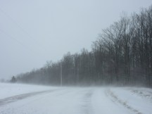 Wind blowing snow across the road.