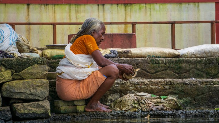 Une femme fait la vaisselle dans un canal d'Alleppey, au Kerala