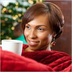women-smiling-wearing-red-blanket-drinking-from-coffee-cup