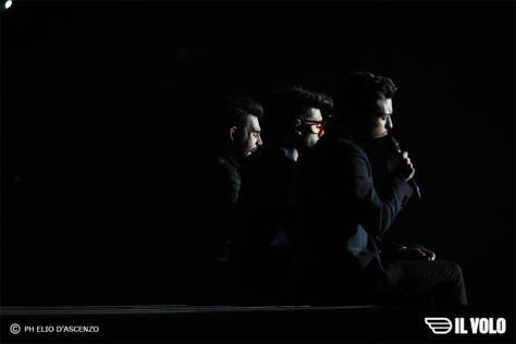 3 in dark sit on stage