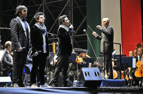 Ignazio, Piero and Gianluca singing on stage while being directed by Maestro Ennio Morricone