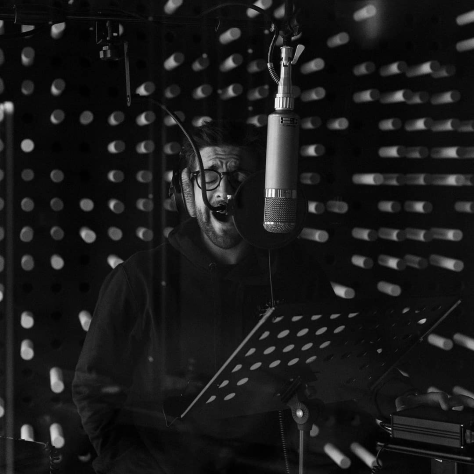 Black and white photo of Piero singing in the recording studio