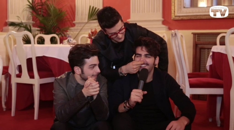 Left to right: Gianluca, Piero and Ignazio sitting on some steps in a restaurant Day 6
