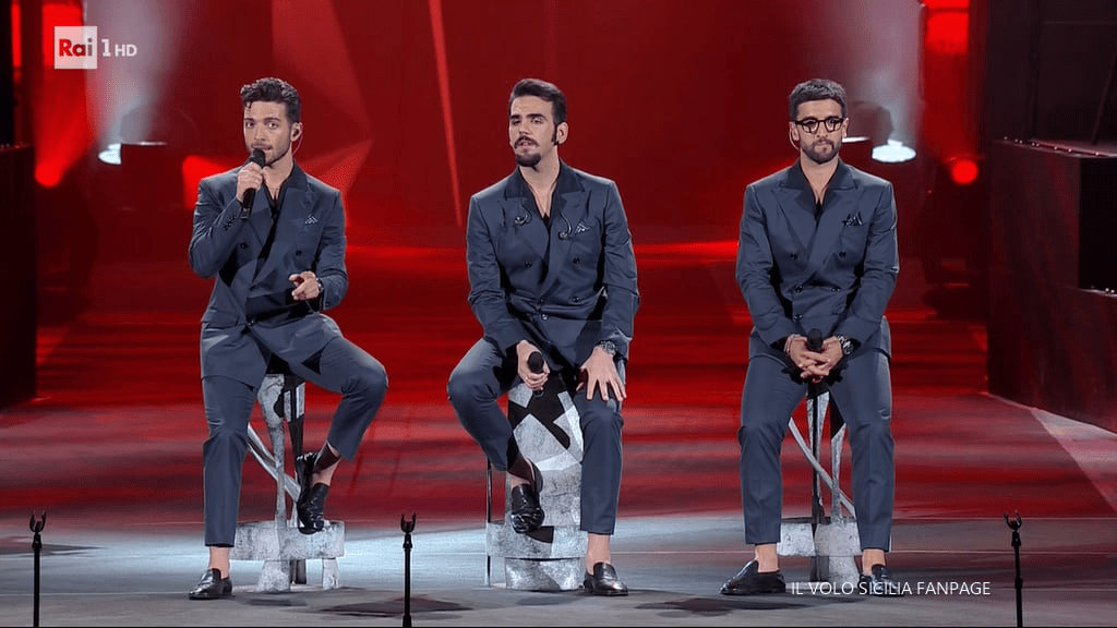 Left to right: Gianluca, Ignazio and Piero sitting and singing on the arena stage