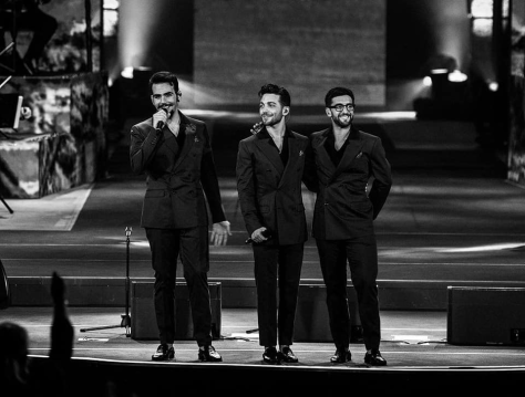 Black and white photo of Piero, Ignazio and Gianluca standing on the stage