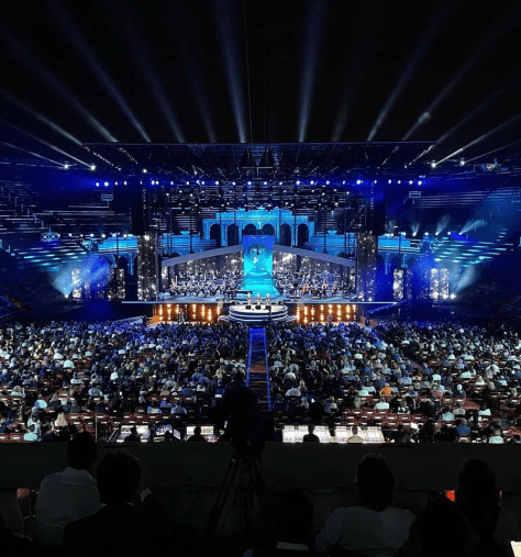 View of the stage lit in blue from the back of the arena