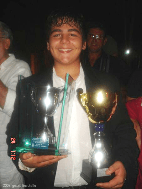 A young Ignazio holding two trophy cups