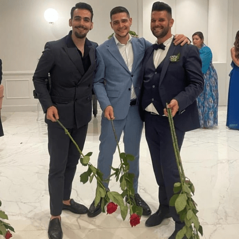 Ignazio on left with two other cousins at wedding holding long stem roses