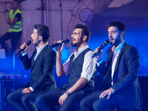 Left to right: Gianluca, Ignazio and Piero sitting and singing on stage