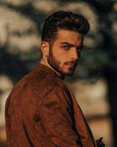 Gianluca in a brown jacket looking over his shoulder