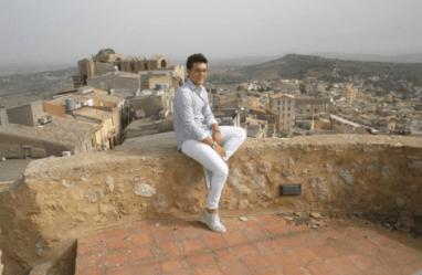Piero sitting on a wall overlooking Naro