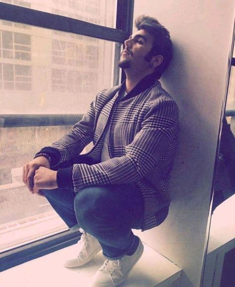 Ignazio squatting on the sill of a window leaning against the side