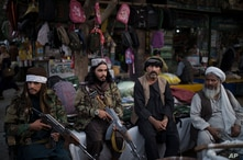Taliban fighters sit next to street vendors at a local market in Kabul, Afghanistan, Friday, Sept. 10, 2021. (AP Photo/Felipe…