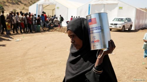 A woman carries a tin of food aid distributed by the WFP, at the Um Rakuba refugee camp which houses Ethiopians fleeing the fighting in the Tigray region, on the the border in Sudan, Dec. 3, 2020.