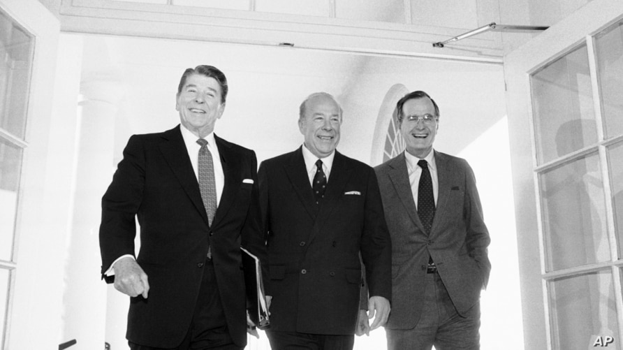 FILE - In this Jan. 9, 1985 file photo, Secretary of State George Shultz, center, walks with President Ronald Reagan and Vice…