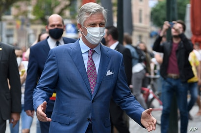 Belgium's King Philippe, wearing a mouth mask, walks down a main shopping street in Brussels, Sunday, May 10, 2020. The Belgian…
