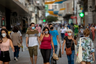 People wearing face masks to prevent the spread of coronavirus walk in downtown Madrid, Spain, Wednesday, Sept. 16, 2020. The