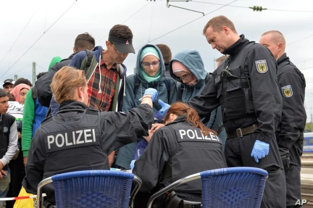 German policemen register refugees at the rail station in Freilassing, southern Germany, Sept. 14, 2015, before they take them away in busses.