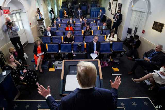 Reporters are seen complying with social distancing norms as President Donald Trump speaks about the coronavirus in the James Brady Press Briefing Room at the White House, April 13, 2020, in Washington.