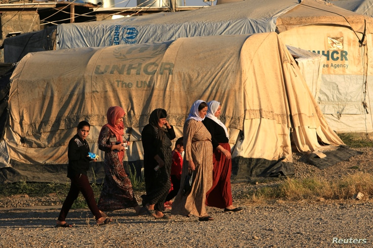 Displaced Iraqi women from the minority Yazidi sect, who fled the Iraqi town of Sinjar, walk at the Khanki camp on the…