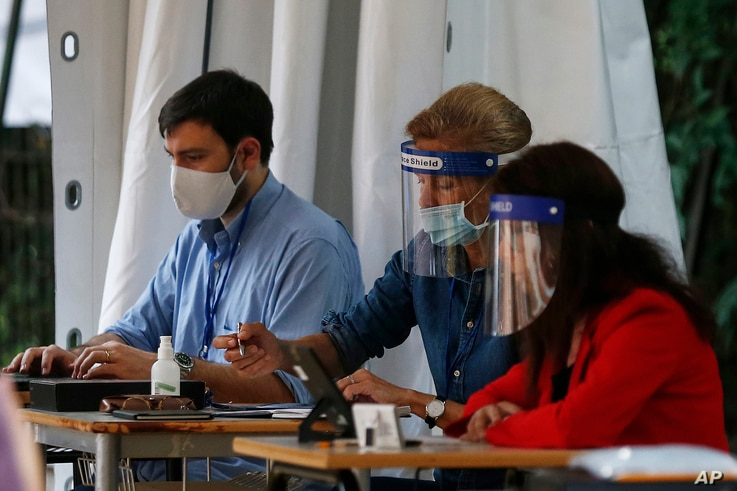 Examiners wear face shields and masks to prevent the spread of COVID-19, during end of year secondary school exams at high school Liceo Kennedy, in Rome, June 17, 2020.