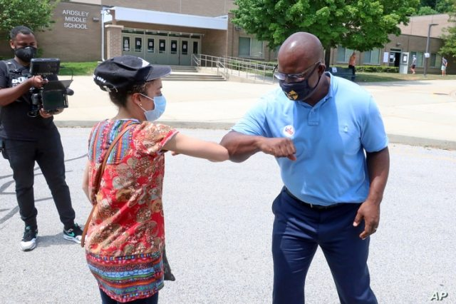 Democratic congressional candidate Jamaal Bowman bumps elbows with a voter outside a voting site in Ardsley, N.Y. on Tuesday,…