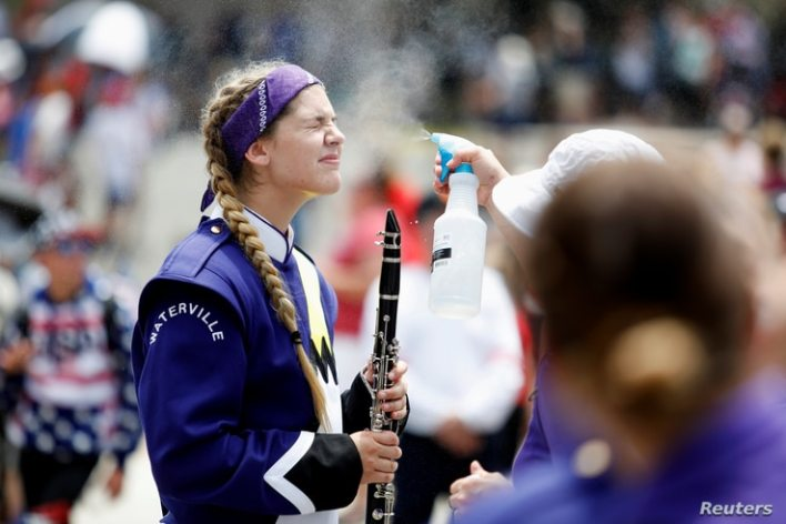 A member of the Waterville Junior/Senior High School marching band is sprayed with water mist to prevent heat stroke while…