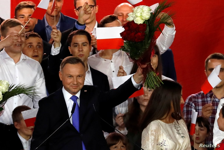 Polish President and presidential candidate of the Law and Justice (PiS) party Andrzej Duda holds up a bouquet after the announcement of the first exit poll results on the second round of the presidential election in Pultusk, Poland, July 12, 2020.