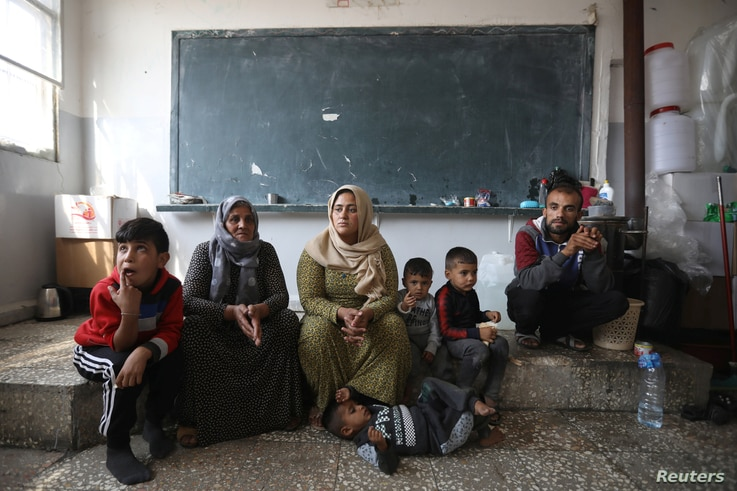 FILE - Members of a displaced Kurdish family sit at a public school they use as a temporary shelter, in Hasakah, Syria, Oct. 22, 2019.