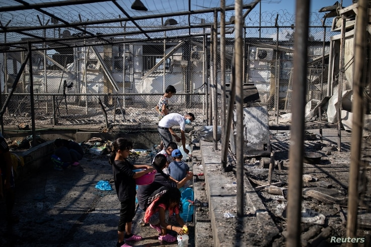 Refugees and migrants gather water next to destroyed shelters following a fire at the Moria camp on the island of Lesbos,…