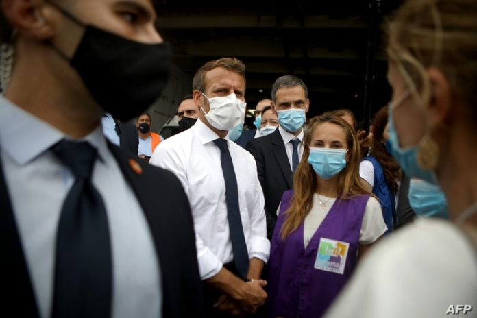 French President Emmanuel Macron, second from the left, listens to members of local NGOs unloading emergency aid delivered to Lebanon at the port of Beirut on September 1, 2020.