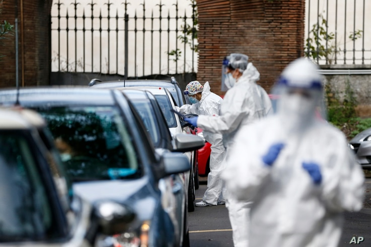 Medical staffers take swabs as they test for COVID-19 at a drive-through, in Rome, Tuesday, Oct. 13, 2020. Italian Premier
