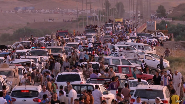 This image made from video taken on Sunday, Aug. 3, 2014 shows Iraqis people from the Yazidi community arriving in Irbil in…