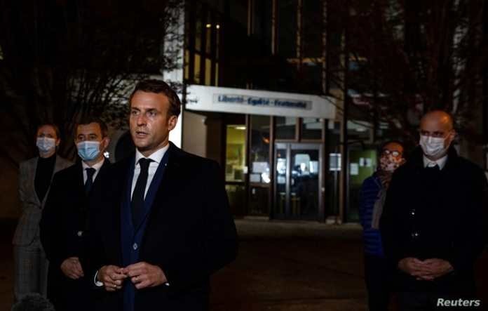 French President Emmanuel Macron, flanked by officials, addresses the press following a knife attack at a school on the outskirts of Conflans-Sainte-Honorine in Paris, France, October 16, 2020.