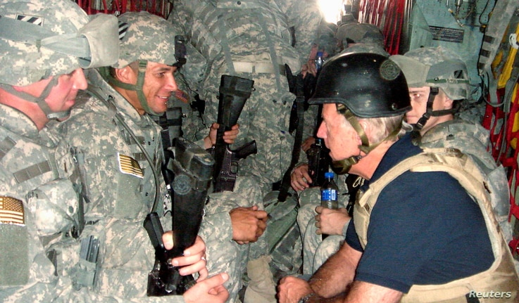 FILE PHOTO: U.S. Senator and Democratic presidential candidate Joe Biden (R) talks with soldiers as he travels in a military…