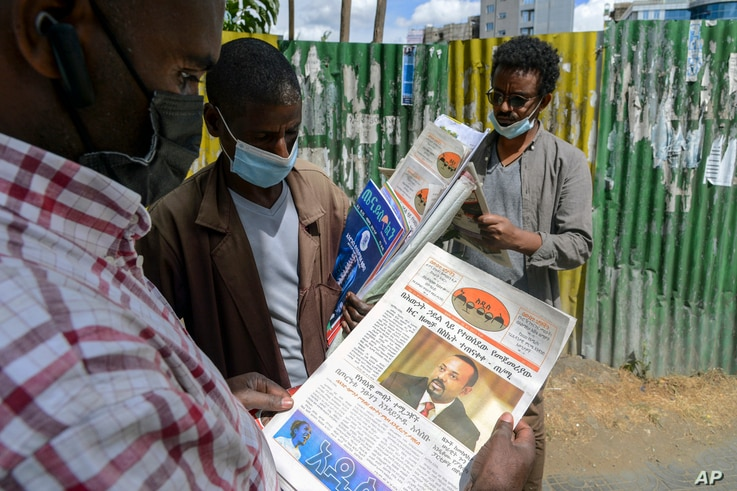 Ethiopians read newspapers and magazines reporting on the current military confrontation in the country, one of which shows a…