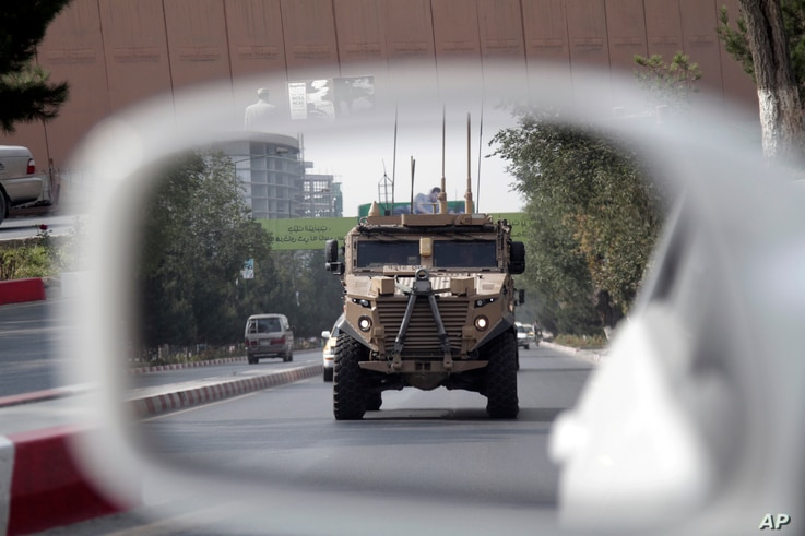 FILE - A patrolling U.S. armored vehicle is reflected in the mirror of a car in Kabul, Afghanistan, Aug. 23, 2017.