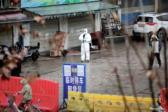 FILE - A worker in a protective suit is seen at a shuttered seafood market during the early spread of the coronavirus, in Wuhan, Hubei province, China Jan. 10, 2020.