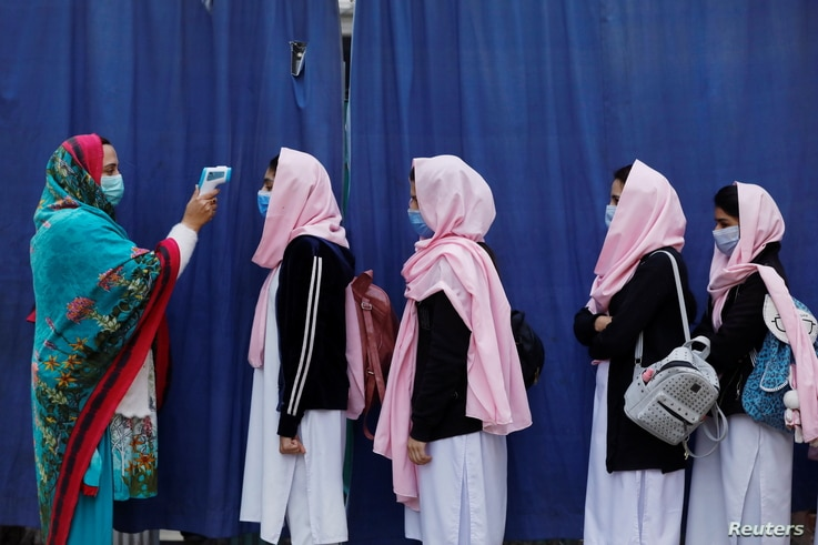 Students wear protective masks as they have their temperature checked before entering classrooms as secondary schools reopen…