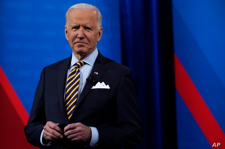 President Joe Biden stands on stage during a break in a televised town hall event at Pabst Theater, Tuesday, Feb. 16, 2021, in…