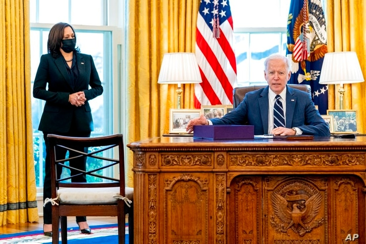 President Joe Biden, accompanied by Vice President Kamala Harris, looks up after signing the American Rescue Plan, a…